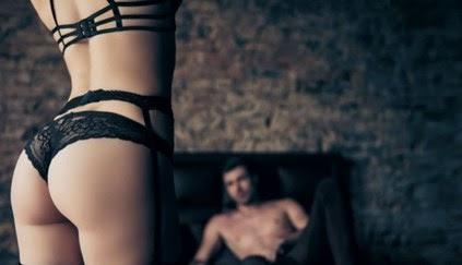 Femme en lingerie debout avec un homme la regardant dans son lit prêt pour un massage sexy.